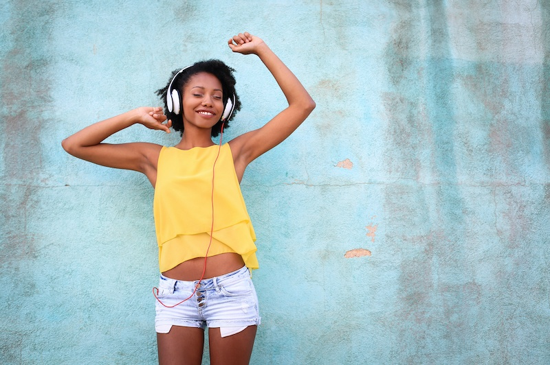 Young woman dancing to music | 12 Self-Care Tips To Get You Through A Pandemic